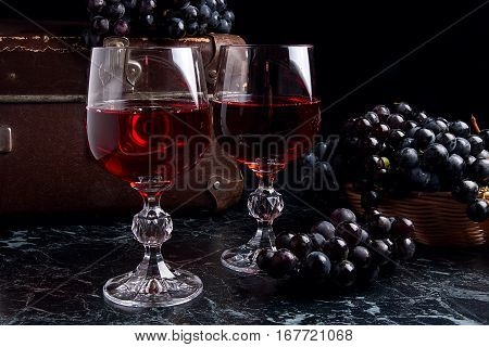 Glass Of Red Wine On Dark Marble Background. Cluster Of Blue Grapes On On Back Background..