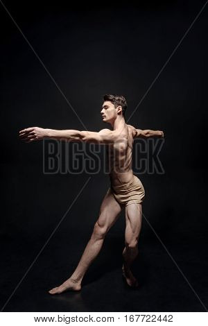 The art of dance. Charismatic graceful male dancer standing in the studio and expressing concentration while stretching against black background and demonstrating his grace