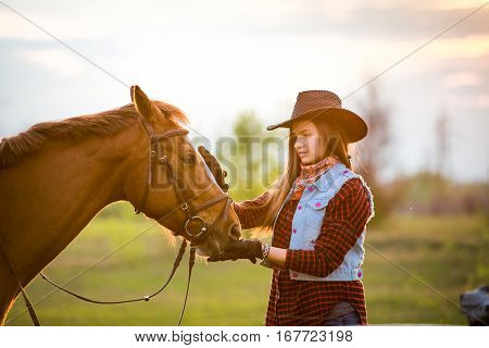 cowgirl in a hat standing near a horse in a field