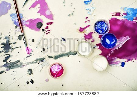 Paint brushes with opened paint buckets on a light background