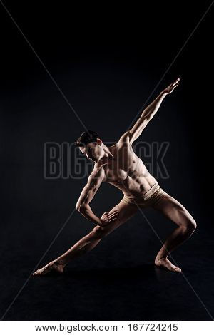 Full of grace. Talented inspired magnetic athlete stretching in the dark lighted studio and showing his abilities while expressing grace