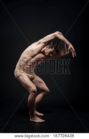 Enjoying my performance. Imaginative flexible graceful actor demonstrating his flexibility and expressing grace while performing in the black colored studio