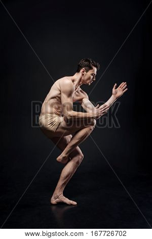 Body labyrinth. Motionless involved masterful gymnast demonstrating his flexibility and expressing creativity while acting against black background
