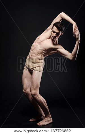 Taking part in the art performance. Skilled athletic young ballet dancer demonstrating his skills and expressing creativity while standing against black background