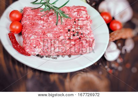 Minced beef on plate - fresh ground beef meat with seasonings on plate close up