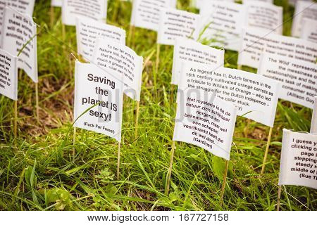 ROTTERDAM THE NETHERLANDS - AUGUST 23 2014: Art instalation in Rotterdam. Lots of tiny banners with qoutes about nature are thrust into green lawn. Save the planet concept