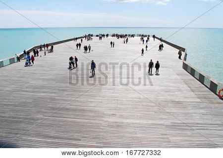 HASTINGS, ENGLAND - APRIL 30, 2016: People walk on the newly restored Victorian pier. Built in 1872, the pier was badly damaged by fire in October 2010 and was finally reopened in April 2016.