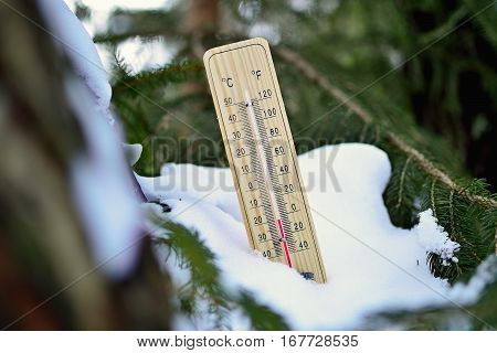 Mercury wooden thermometer stuck on snow in forest shows very low temperatures. Temperatures in Celsius and Fahrenheit degrees. Cold winter weather. Twenty degrees under zero during the day.