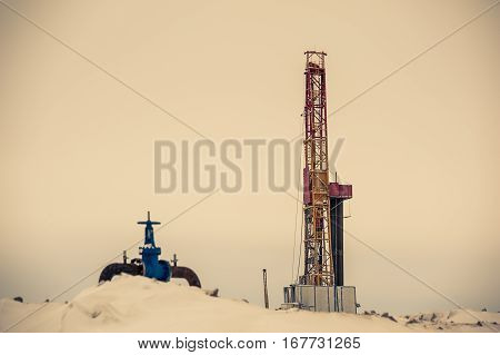 Pump jack and oil rig in the oilfield situated in the beautiful winter forest. Environmental pollution. Oil and gas concept.