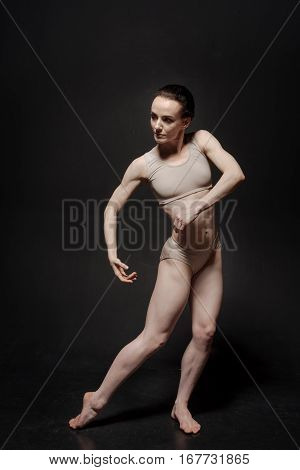Involved in my thoughts. Gracious proficient young ballet dancer performing isolated in the black colored studio and expressing elegance while dancing