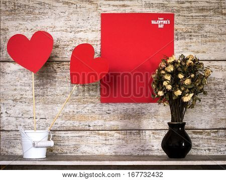Valentine's Day card with paper hearts on sticks in a bucket. With copy space. On a wooden background