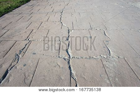 big break on damaged stamped fissure concrete cracked pavement, timeworn appearance colors textures of paving slate stone tile on cement, broken flooring exterior decorative surfaces