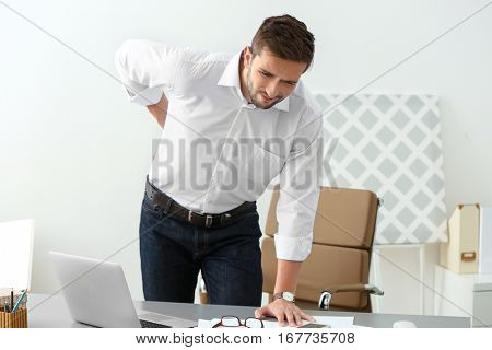 Handsome young man suffering from backache in office