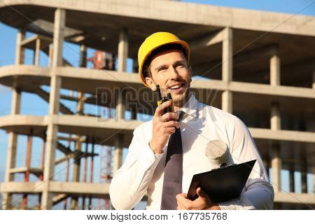 Handsome engineer with portable radio transmitter and clipboard standing against unfinished building