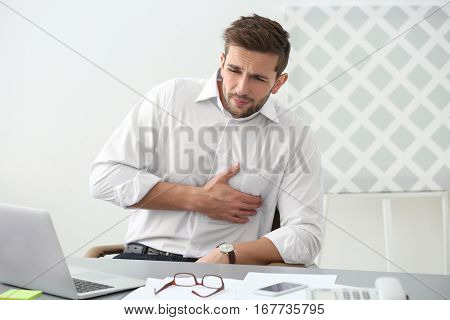 Handsome young man suffering from heartache in office