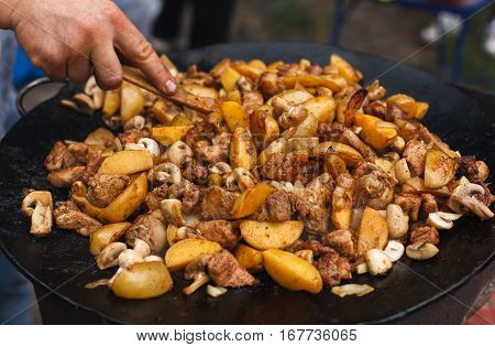 Country fair, vendor cooking. Roasted potatoes with meat and mushroomes cooked outdoors in big metal cauldron pot. Cookout meals. Fresh snack on grill flame. Street fast food.