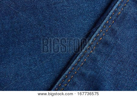 Dark blue grunge textile surface background close up with yellow stitches