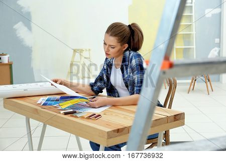 Young female decorator choosing colors for new flat