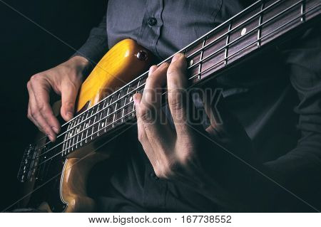 Rock music background bass guitar player closeup photo with selective focus and motion blur effect