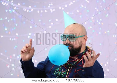 Funny fat man inflating balloon at birthday party