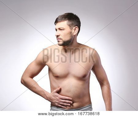 Young man with stomach pain on color background