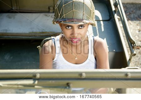 beautiful smiling black young girl with ww2 military helmet