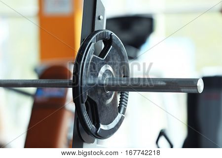 Barbell on rack in gym, close up
