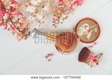 There White and Pink  Branches of Chestnut Tree,Brown Powder with Mirrow and Make Up Brush are on White Table,Top View