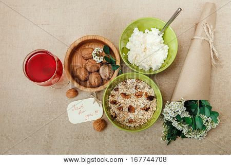 Healthy Organic Breakfast.Walnuts,Oatmeal andC ottage Cheese.Green Ceramic and Wooden Plates.Glass with Red Drink.Wish Yellow Card with Bouquet.Top View