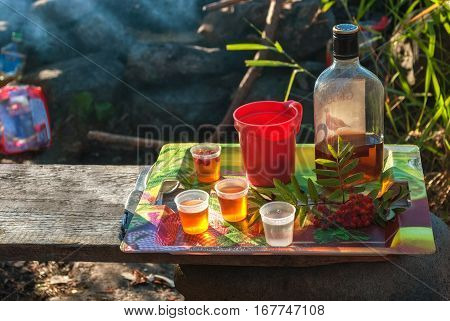 Bottle of cognac liqueur glasses mug and a sprig of mountain ash mug on tray standing on a wooden board.