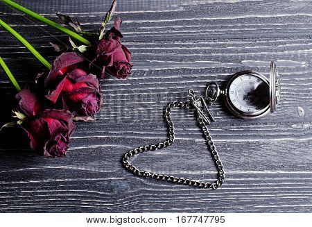 Three beautiful dry roses and an antique pocket watch with a heart-shaped chain against an aged wooden background (retro toned vintage style)