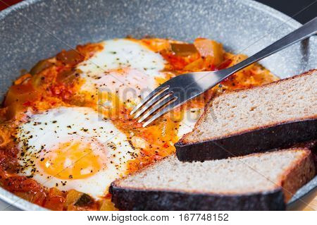 Delicious homemade shakshouka in a pan closeup. Traditional Middle East cuisine