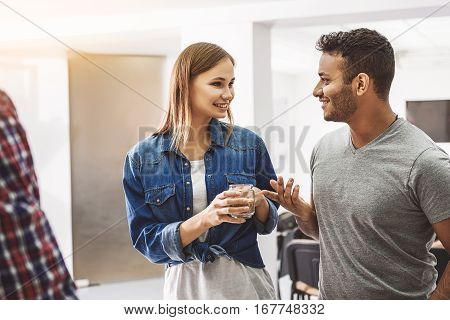 Hilarious young persons are looking at each other. Woman is holding small jar with coffee
