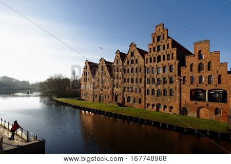 LUBECK, GERMANY - DECEMBER 30, 2016: Salt storehouses at the bank of river Trave. Because of its extensive Brick Gothic architecture, the city is listed by UNESCO as a World Heritage Site