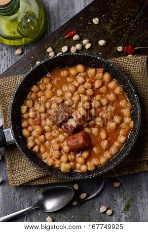 high-angle shot of a stone frypan with garbanzos a la riojana, a spanish chickpeas stew, on a wooden chopping board placed on a rustic wooden table next to a cruet with olive oil