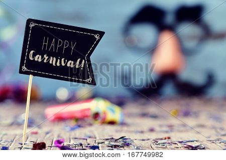 closeup of a black flag with the text happy carnival on a wooden surface full of confetti, a party horns and a pair of fake black glasses, a nose and a mustache in the background