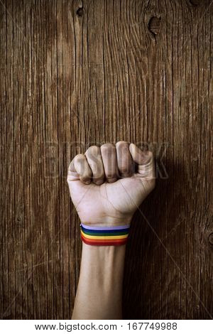 closeup of a young caucasian man with a band patterned as the rainbow flag tied to his wrist and his fist raised against a rustic wooden background with a blank space