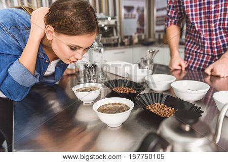 Curious young woman is standing near metal table. She inclining to white round bowl with invigorating drink