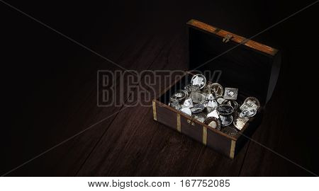 treasure chest with coins medals and bars of pure silver and copy space