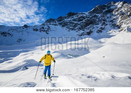 Mountaineer backcountry ski walking up along a snowy ridge with skis in the backpack. In background blue sky and shiny sun and Ortler in South Tirol, Italy.  Adventure winter extreme sport.