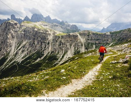 View of cyclist riding mountain bike on trail in Dolomites,Tre Cime di Laverado, South Tirol, Italy