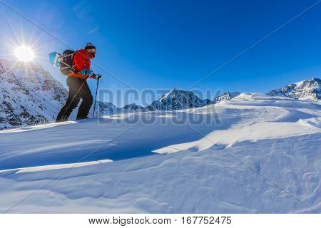 Hiker in winter mountains snowshoeing climbing to the top in sunny cold day in Alps, Italy.