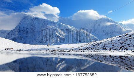Panoramic view of Annapurna 3 III and Ganggapurna mirroring in Ice Lake or Kicho Tal Annapurna range way to Thorung La pass Annapurna circuit trek Nepal