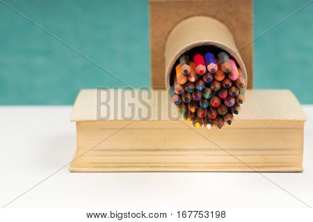Multicolored pensils in the box on the book. Back to school. Copy space. Top view.
