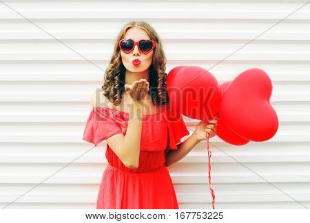 Portrait Cute Woman In Red Dress Sends Air Kiss With Balloon Heart Shape Over White Background