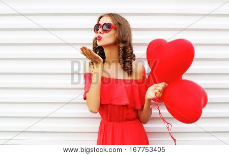 Portrait Woman In Red Dress Sends Air Kiss With Balloon Heart Shape Over White Background