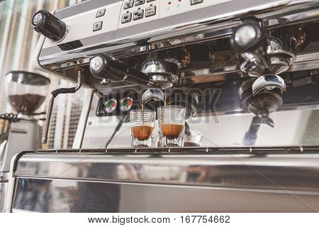 Two half-filled glasses full of dark coffee near special apparatus