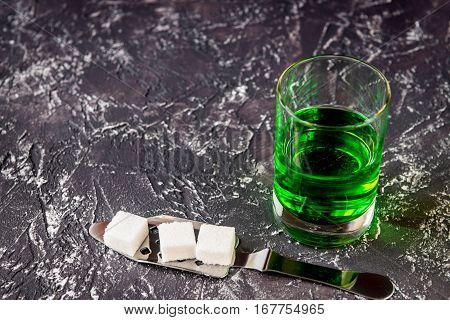 absinthe in glass on gray background close up.