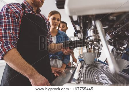 Man is standing near coffee machine. Visitors are looking at him with attention