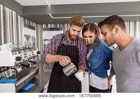 People are standing near man, who is taking metal bowl with crema and cup of coffee